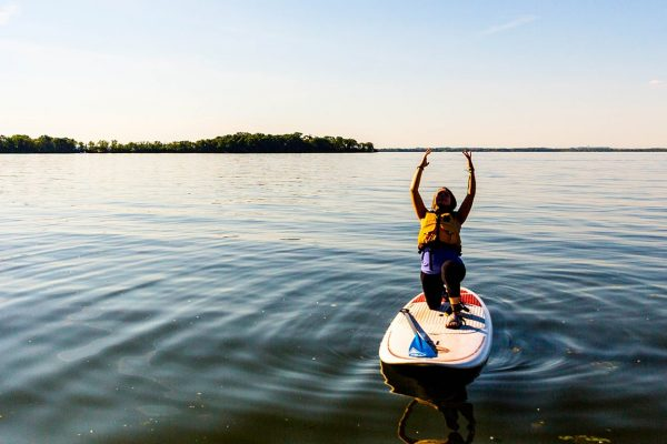 paddleboarder doing yoga on a calm Lake Mendota with Picnic Point in background