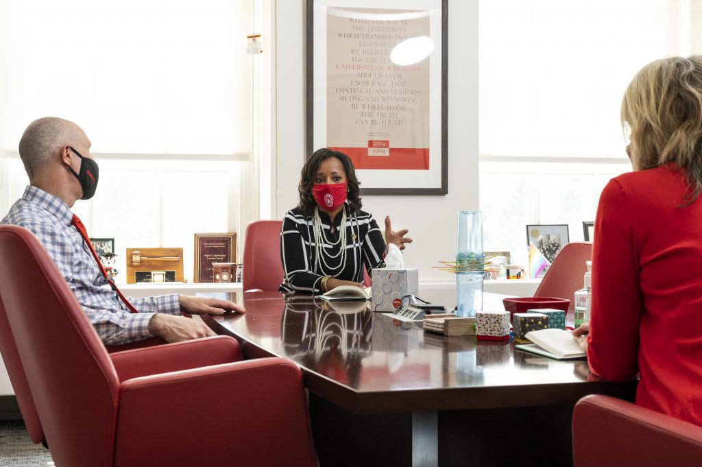 Wearing a face mask and physical distancing during the global coronavirus (COVID-19) pandemic, Cheryl Gittens, interim deputy vice chancellor for diversity and inclusion and chief diversity officer at the University of Wisconsin-Madison, is pictured talking with Lori Reesor, vice chancellor for student affairs, and Argyle Wade, chief of staff, in Reesor's office in Bascom Hall on September 23, 2020.