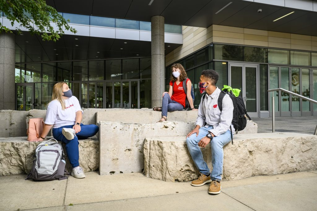 Wearing face masks and maintaining physical distance from others during the global coronavirus (COVID-19) pandemic, undergraduate students sit and talk near the Discovery Building at the University of Wisconsin-Madison during summer on Aug. 1, 2020
